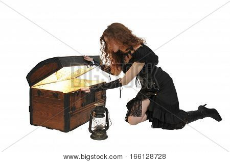 Beautiful young woman pirate opening a treasure chest