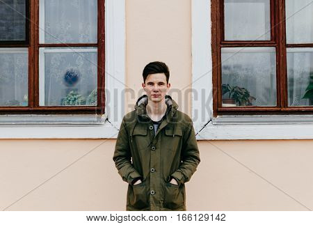 Young man and wall of house with windows in the city