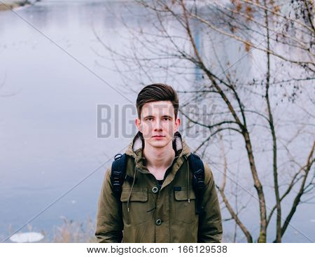 Portrait of the young man on the city river in wautumn time