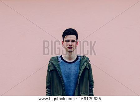 Young man portrait on the pink wall background