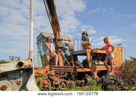 Three sexy attractive women stand on old agriculture harvester in farm