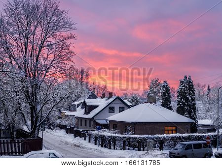Red and orange winter sky - sunset in the small snowy town in Latvia