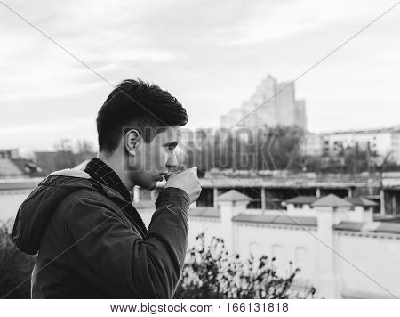 Young man drinking coffe on the city street in autumn time