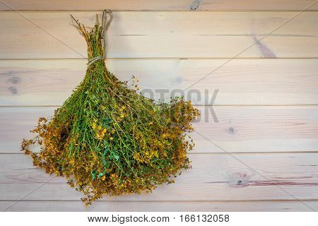 Dried St. John's wort is hanging on a wooden wall