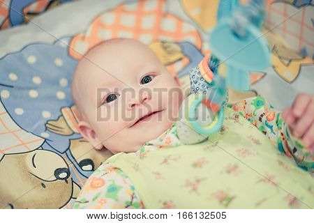 Baby lying in bed and smiling. Boy watches and watches with interest. Cozy home warm atmosphere