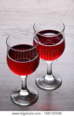 glass of red wine. A couple of glasses of wine on a light wooden background