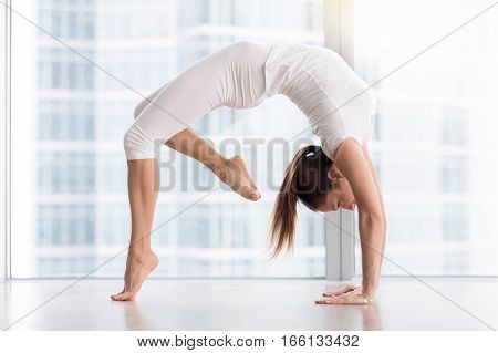 Young attractive woman practicing yoga, stretching in Urdhva Dhanurasana exercise, Bridge pose, working out, wearing sportswear, white t-shirt, pants, indoor full length, floor window with city view