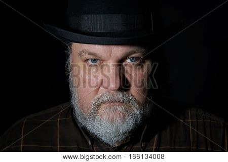 Portrait of the man with gray beard in black hat on the black background