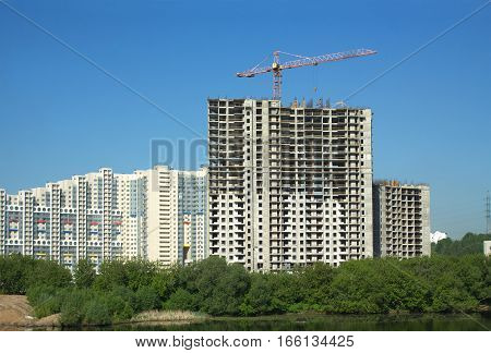 Long hoisting tower crane in construction new apartment building process over cloudless sky