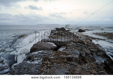 stone road disappearing into the distance icy sea the Gulf of Finland in winter