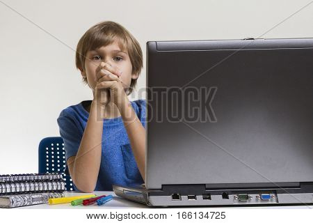 Unhappy tired bored boy sitting near laptop pc. Computer, education, studying concept