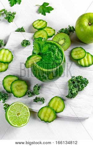 Fresh Green smoothie with kale, cucumber, lime, apple, parsley on white board