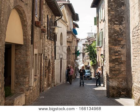 SIRMIONE, ITALY - MAY 5, 2016: Picturesque narrow town street in Sirmione Lake Garda Italy.