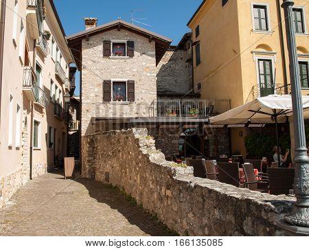 TORRI DEL BENACO, ITALY - MAY 4, 2016: Old street and picturesque houses of Torri del Benaco. Garda Lake Italy