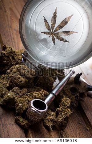 Marijuana buds in glass jars with pipe