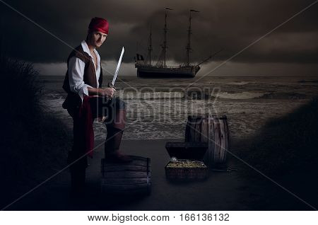 Young pirate posing on a barrel next to the sea