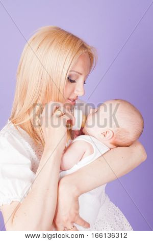 mom feeds the baby from the bottle with teat 1