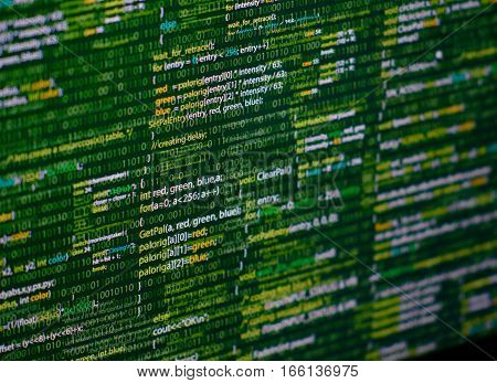Programming abstract - source code and binary code on display of software developer. Green theme.