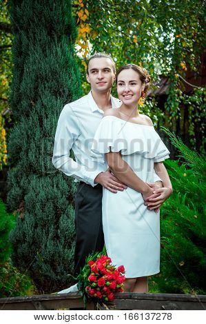 Happy loving wedding couple hugging in the autumn park. Young handsome groom embracing his beautiful smiling bride in white dress