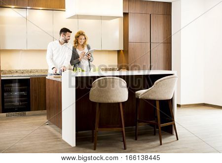 Couple In Home Kitchen Using Tablet