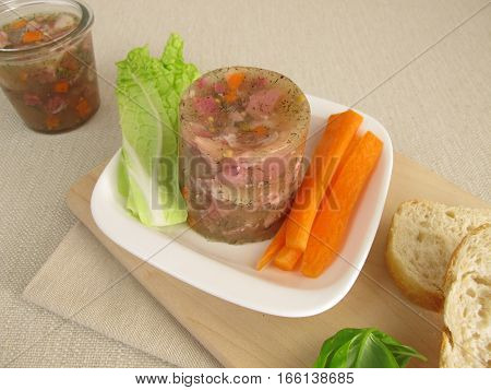 Homemade brawn in jar with salad and roll