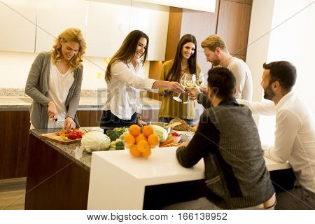 Group Of Young People Having Dinner And Drinking Wine In Modern Kitchen