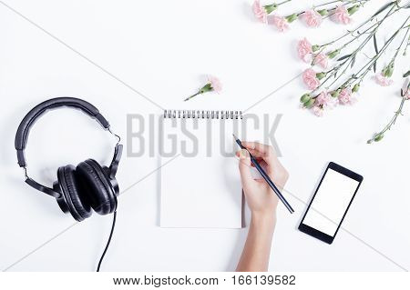 Female Hand Writing In A Notebook, Mobile Phone, Headset And Flowers On A White Background