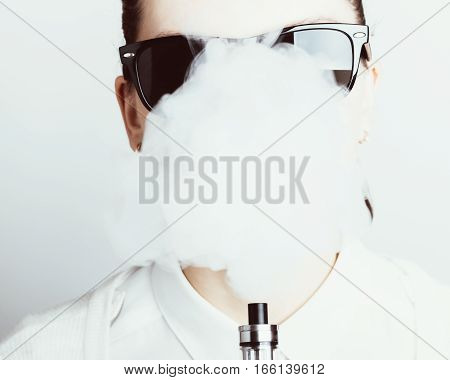 Close-up of a woman exhales vapor from an electronic cigarette portrait