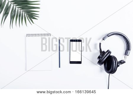 Mobile Phone, Black Headphones, Notebook, Pencil And Green Leaves Lie On A White Table