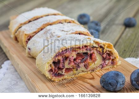 Detail On Plum Strudel On Wood Plank Timber With Fresh Plums