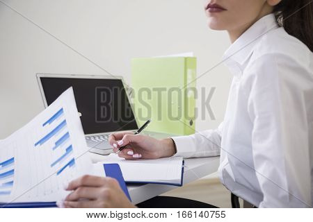 Close up of woman's hands writing in a notebook and holding a diagram attached to a clipboard. Concept of paperwork. Mock up