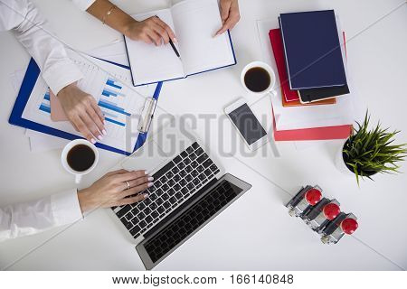 Top view of two pairs of women's hands on a table surface. There is a laptop a smartphone and a clipboard on it. One girl is typing the second is holding a pen