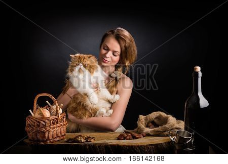 The beautiful girl in a sundress from a canvas sits at an oak table with a young remarkable red Persian cat on hands near a basket with onions and garlic, dried mushrooms and a bag with chestnuts