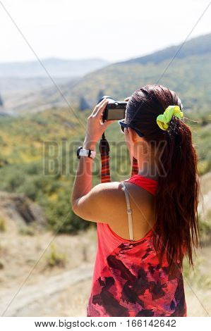 Girl photographed against backdrop of panoramic view of mountains