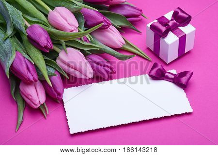 Greeting card, a bouquet of spring tulips, gifts in a beautiful package, bow from satin ribbon, the gift set on a pink background