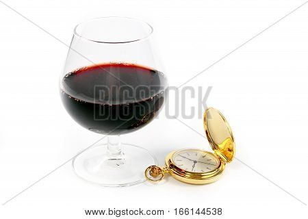 glass of strong red wine and pocket watch in gold case as a symbol of good luck and success