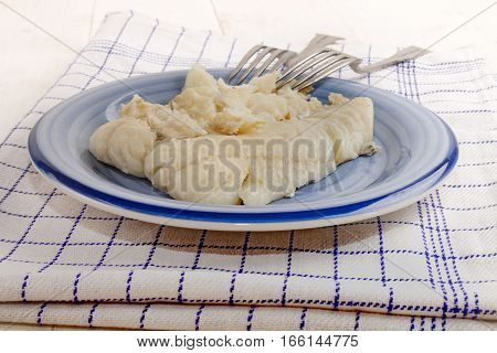 cooked hake filet on a plate with fork