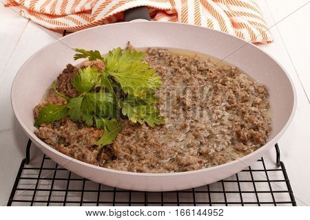 fried pork minced meat with oil and parsley in a pan on a cooling rack