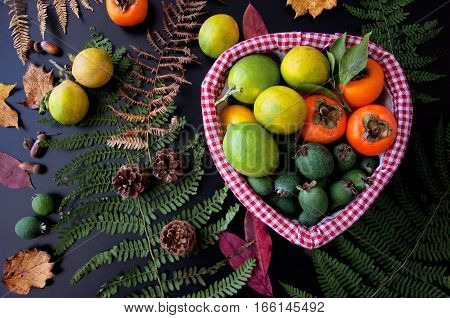 Fruits in basket: persimmons, lemons, pineapple guava with autumn leaves. Lemon Fresh fruit Persimmon Feijoa Fern Wicker basket Dark background Hands