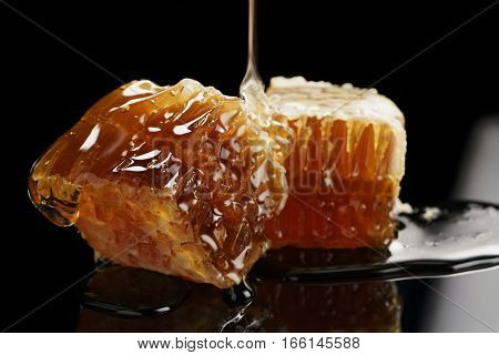 two pieces of organic honeycomb with honey isolated on black background with reflection