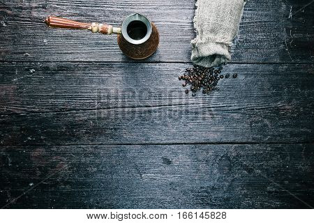 Sack of coffee beans with pot on the table. Overhead view