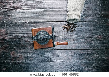 Sack of coffee beans with hand grinder on the table. Overhead view