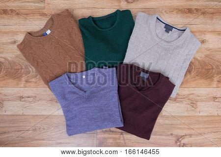 Winter Clothes Collection On Wooden Background