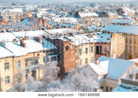 Winter view on the old town with snowbound roofs in Lviv city, Ukraine. Tilt-shift image technic