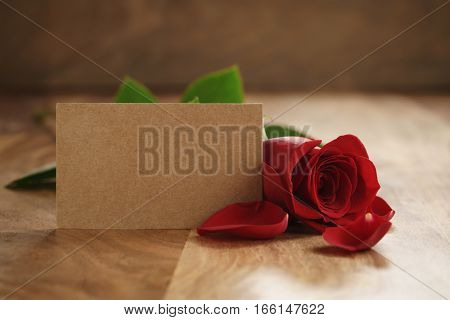 beautiful red rose with petals and empty paper card on old wood table, romantic background with copy space
