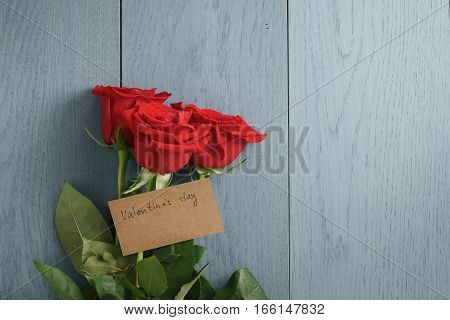 three red roses on blue wood table with valentines day paper card, with copy space