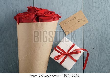 bouquet of red roses on blue wood table with gift and valentines day paper card from above, top view