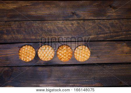Four round pastry on dark wooden background