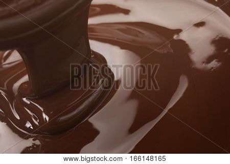 melted dark premium chocolate pour from above, slightly toned photo