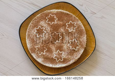 Christmas coffee cake with creamy souffle decorated star on beige wood. Aerial view.